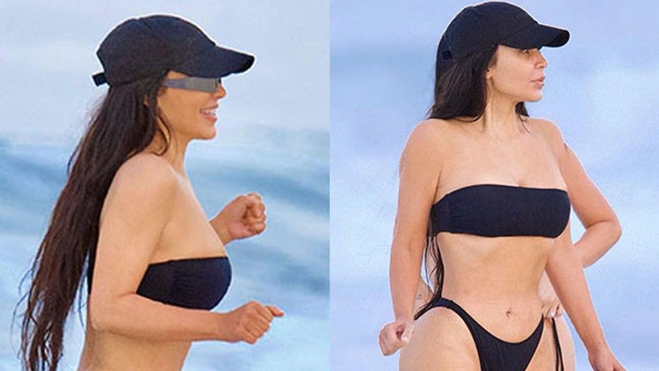 Kim Kardashian flaunts figure in cheeky black bikini during beach outing