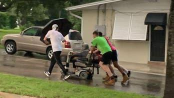 4 men push elderly woman in broken scooter home in pouring rain