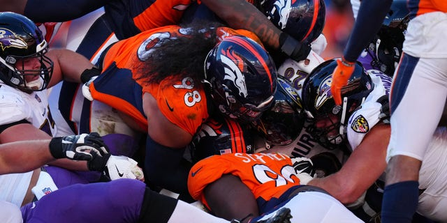Oct 3, 2021; Denver, Colorado, USA; Baltimore Ravens running back Latavius Murray (28) is tackled by Denver Broncos nose tackle Mike Purcell (98) and linebacker A.J. Johnson (45) and defensive tackle Shamar Stephen (99) in the second half at Empower Field at Mile High.
