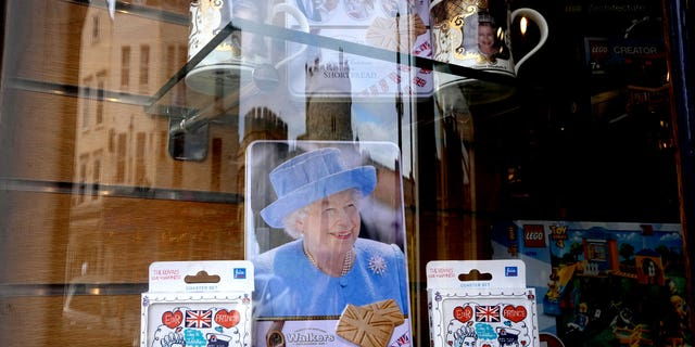 Windsor Castle is reflected in the window of a shop selling royal souvenirs outside the castle in Windsor, England, Friday, Oct. 22, 2021. (AP Photo/Kirsty Wigglesworth)