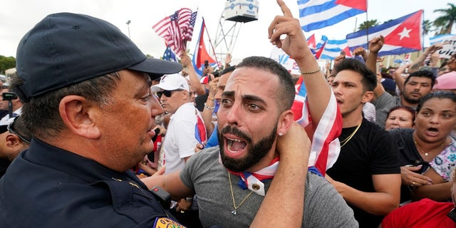 This Wednesday, July 14, 2021, File Photo, Miami Police Chief Art Acevedo, left, embraces a demonstrator in Miami's Little Havana neighborhood, as people support antiguerment demonstrations in Cuba.  Miami city commissioners held a special meeting last month in which they attacked Acevedo's post in less than six months and voted to further investigate him and his appointment.  (AP Photo / Wilfredo Lee, File)