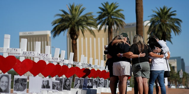 In this Oct. 1, 2019, file photo, people pray at a makeshift memorial for shooting victims in Las Vegas, on the anniversary of the mass shooting two years earlier. People who died, will be remembered Friday, Oct. 1, 2021, during the fourth anniversary of the Las Vegas massacre that became the deadliest mass shooting in modern U.S. history.