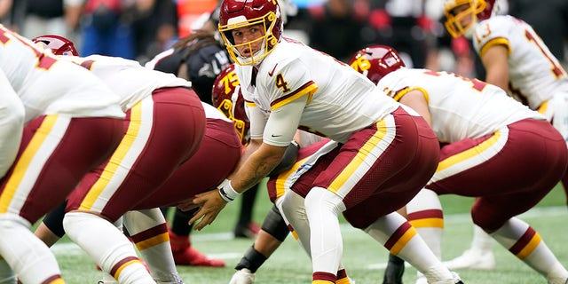 Washington Football Team quarterback Taylor Heinicke (4) works against the Atlanta Falcons during the first half of an NFL football game, Sunday, Oct. 3, 2021, in Atlanta. (AP Photo/Brynn Anderson)