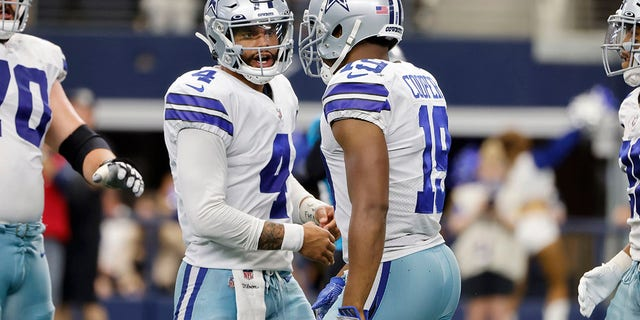 Dallas Cowboys quarterback Dak Prescott (4) and wide receiver Amari Cooper (19) celebrate Cooper's touchdown catch in the second half of an NFL football game against the Carolina Panthers in Arlington, Texas, Sunday, Oct. 3, 2021.