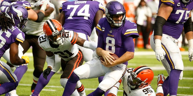 Minnesota Vikings quarterback Kirk Cousins (8) is sacked by Cleveland Browns cornerback Denzel Ward (21) and defensive end Myles Garrett (95) during the second half of an NFL football game, Sunday, Oct. 3, 2021, in Minneapolis. (AP Photo/Bruce Kluckhohn)