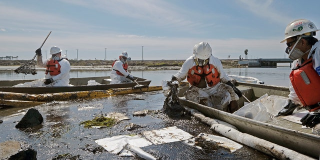 Cleanup contractors deploy skimmers and floating barriers known as booms to try to stop further oil crude incursion into the Wetlands Talbert Marsh in Huntington Beach, Calif., Sunday., Oct. 3, 2021. (AP Photo/Ringo H.W. Chiu)