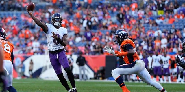 Baltimore Ravens quarterback Lamar Jackson (8) throws as Denver Broncos linebacker A.J. Johnson pursues during the second half of an NFL football game, Sunday, Oct. 3, 2021, in Denver.