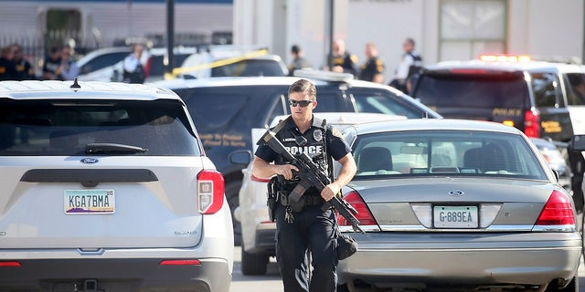 A Tucson Police Department officer walks with his weapon near the scene of a shooting aboard an Amtrak train in downtown Tucson, Ariz., on Monday where a DEA agent and suspect were left dead. (Mamta Popat/Arizona Daily Star via AP)
