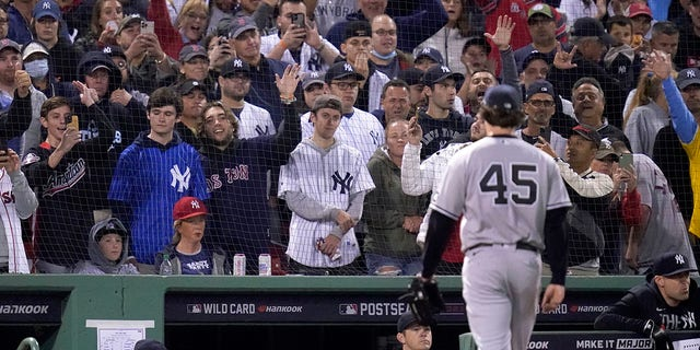 Fans react as New York Yankees starting pitcher Gerrit Cole (45) is taken out in the third inning of an American League Wild Card playoff baseball game against the Boston Red Sox at Fenway Park, Tuesday, Oct. 5, 2021, in Boston. (AP Photo/Charles Krupa)