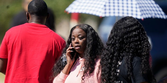 People gather on a road leading to Timberview High School after a shooting at the school in south Arlington, Texas on Wednesday. (AP Photo/LM Otero)