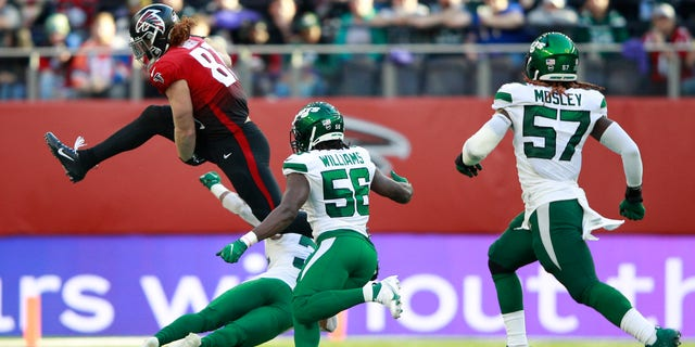 Atlanta Falcons tight end Hayden Hurst (81) leaps over a tackle during the second half of an NFL football game between the New York Jets and the Atlanta Falcons at the Tottenham Hotspur stadium in London, England, Sunday, Oct. 10, 2021.