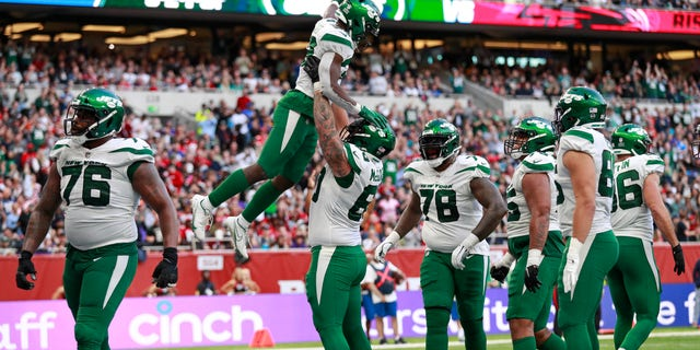 New York Jets running back Michael Carter (32), top center, celebrates after scoring a touchdown during the second half of an NFL football game between the New York Jets and the Atlanta Falcons at the Tottenham Hotspur stadium in London, England, Sunday, Oct. 10, 2021.