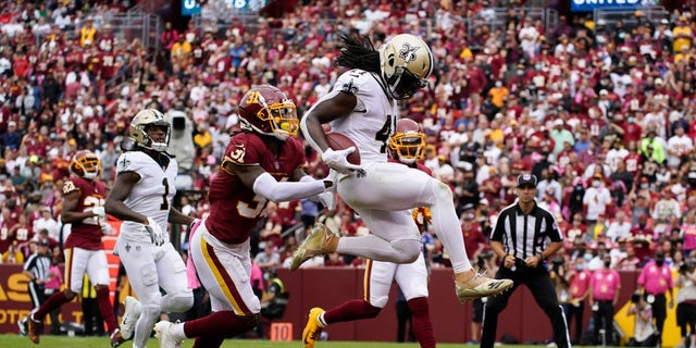New Orleans Saints running back Alvin Kamara, right, scores a touchdown in front of Washington Football Team free safety Kamren Curl in the first half of an NFL football game, Sunday, Oct. 10, 2021, in Landover, Md.