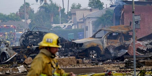 تعمل فرق الإطفاء في موقع حادث تحطم طائرة صغيرة ، يوم الاثنين 11 أكتوبر 2021 ، في سانتي ، كاليفورنيا.