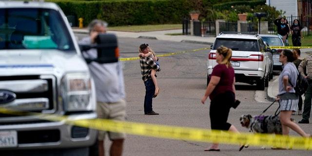 الجيران يشاهدون طواقم الإطفاء بالقرب من مكان تحطم طائرة صغيرة ، الاثنين 11 أكتوبر 2021 ، في سانتي ، كاليفورنيا. قتل شخصان على الأقل وأصيب اثنان آخران عندما تحطمت الطائرة في أحد ضواحي جنوب كاليفورنيا ، مما أدى إلى مقتل شخصين. وقالت السلطات إن النيران تحترق.  (AP Photo / جريجوري بول)