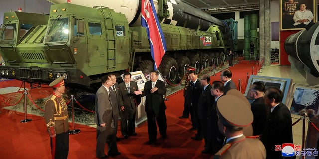 In this photo provided by the North Korean government, North Korean leader Kim Jong Un, center, speaks in front of what the North says is an intercontinental ballistic missile displayed at an exhibition of weapons systems in Pyongyang, North Korea, on Monday.