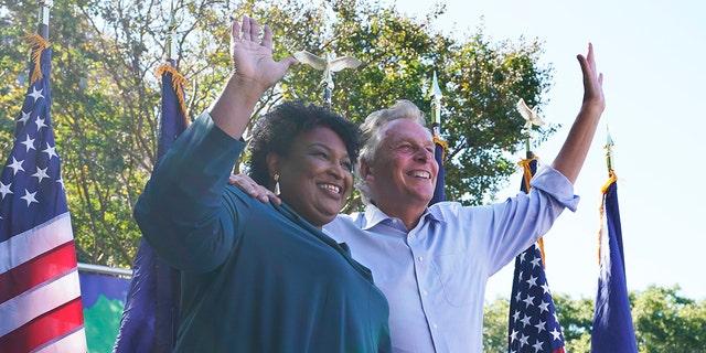La activista por los derechos de voto Stacey Abrams, a la izquierda, saluda a la multitud con el candidato demócrata a gobernador, el ex gobernador de Virginia, Terry McAuliffe, a la derecha, en un mitin en Norfolk, Virginia, el domingo 17 de octubre de 2021. Abrams estuvo en la ciudad para alentar a los votantes a votar por el Partido Demócrata. candidato a gobernador en las elecciones de noviembre.  (Foto AP / Steve Helber)