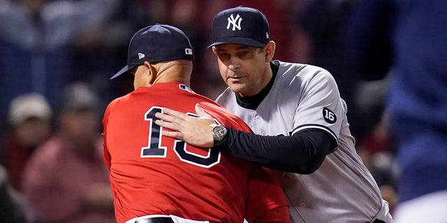 New York Yankees manager Aaron Boone, right, greets Boston Red Sox manager Alex Cora before an American League Wild Card baseball game at Fenway Park, Tuesday, Oct. 5, 2021, in Boston.