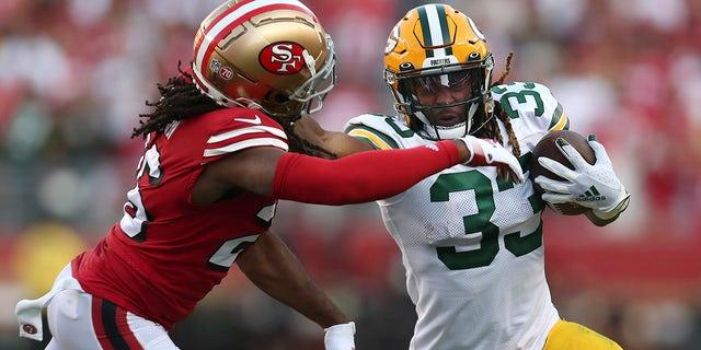 Green Bay Packers running back Aaron Jones (33) runs against San Francisco 49ers cornerback Josh Norman during the first half of an NFL football game in Santa Clara, Calif., Sunday, Sept. 26, 2021.