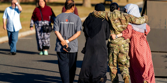 FILE: A female member of the military puts her arms around two female Afghan refugees after they spoke with Secretary of Defense Lloyd Austin as he visits an Afghan refugee camp on Joint Base McGuire Dix Lakehurst, N.J.