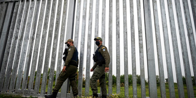 FILE: Police officers patrol alongside a steel wall at Evros river, near the village of Poros, at the Greek-Turkish border, Greece.
