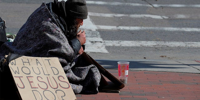 """Billy, who has been experiencing homelessness for seven years, sits with a sign reading """"What Would Jesus Do?"""" amid the coronavirus disease outbreak in Boston, April 15, 2020. (REUTERS/Brian Snyder("""