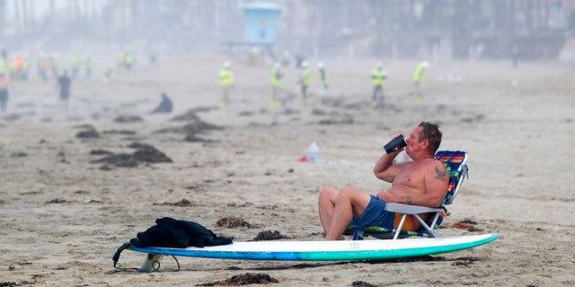 A man rests as workers in protective suits continue to clean the contaminated beach in Huntington Beach, Calif., Monday, Oct. 11, 2021. Huntington Beach reopened its shoreline this morning after water testing results came back with non-detectable amounts of oil associated toxins in ocean water, city officials and California State Parks announced.