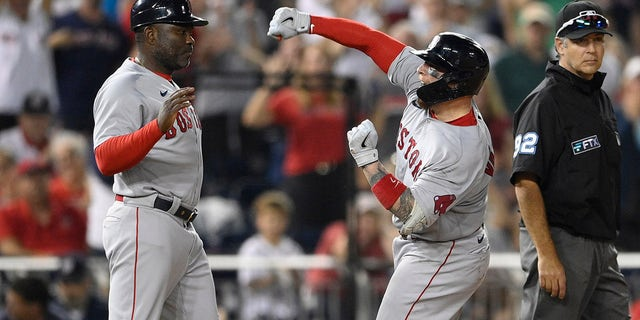 Boston Red Sox's Christian Vazquez, center, reacts at third after he tripled during the ninth inning of a baseball game against the Washington Nationals, Saturday, Oct. 2, 2021, in Washington. At left is Red Sox third base coach Carlos Febles. Red Sox's Jose Iglesias scored on the play. The Red Sox won 5-3