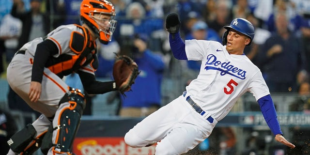 The Los Angeles Dodgers' Corey Seager scores on a double by Trea Turner, ahead of a throw to San Francisco Giants catcher Buster Posey during the first inning of Game 4 of a baseball National League Division Series, Tuesday, Oct. 12, 2021, in Los Angeles.