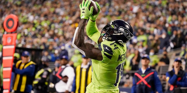 Seattle Seahawks wide receiver DK Metcalf catches a pass from backup quarterback Geno Smith for a touchdown against the Los Angeles Rams during the second half of an NFL football game, Thursday, Oct. 7, 2021, in Seattle.