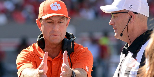 Clemson Tigers head coach Dabo Swinney (left) talks to an official during the first half against the North Carolina State Wolfpack at Carter-Finley Stadium.