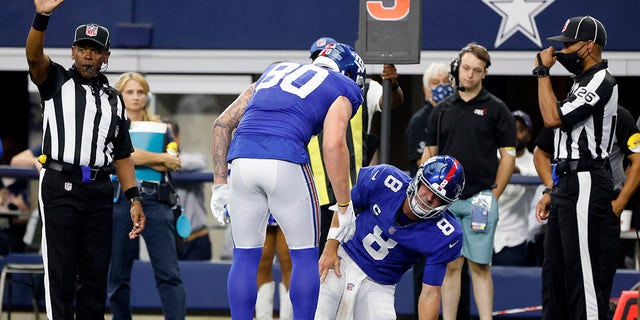 New York Giants tight end Kyle Rudolph (80) checks on quarterback Daniel Jones (8) after Jones was tackled short of the end zone in the first half against the Dallas Cowboys in Arlington, Texas, Sunday, Oct. 10, 2021. Jones suffered an unknown injury on the play.