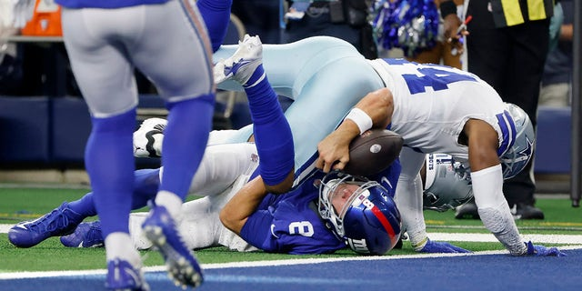 Dallas Cowboys linebacker Jabril Cox (14) tackles New York Giants quarterback Daniel Jones (8) short of the end zone in the first half of a game in Arlington, Texas, Sunday, Oct. 10, 2021. Jones left the game with an unknown injury.