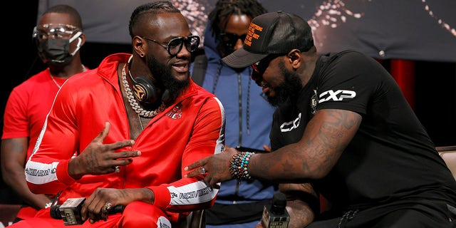 Deontay Wilder (L) talks with his head coach Malik Scott during a news conference at MGM Grand Garden Arena on Oct. 6, 2021 in Las Vegas.