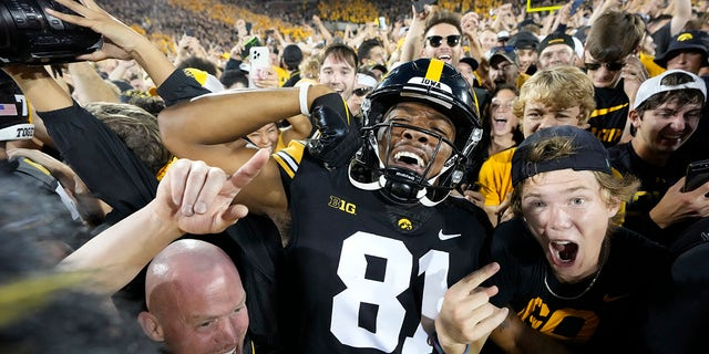 Iowa wide receiver Desmond Hutson (81) celebrates with fans on the field after Iowa beat Penn State 23-20, in an NCAA college football game, Saturday, Oct. 9, 2021, in Iowa City, Iowa.