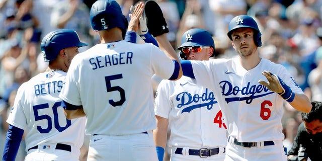 تريا تورنر من فريق Los Angeles Dodgers ، إلى اليمين ، تحصل على تهنئة من Corey Seager (5) ، و Mookie Betts (50) ، و Matt Beaty (45) ، بعد أن ضرب Turner بطولة كبرى على أرضه ضد Milwaukee Brewers خلال الشوط الخامس من لعبة البيسبول مباراة في لوس أنجلوس يوم الأحد 3 أكتوبر 2021.