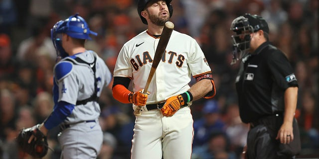 San Francisco Giants' Evan Longoria, middle, reacts after striking out against the Los Angeles Dodgers during the seventh inning of Game 5 of a baseball National League Division Series Thursday, Oct. 14, 2021, in San Francisco.