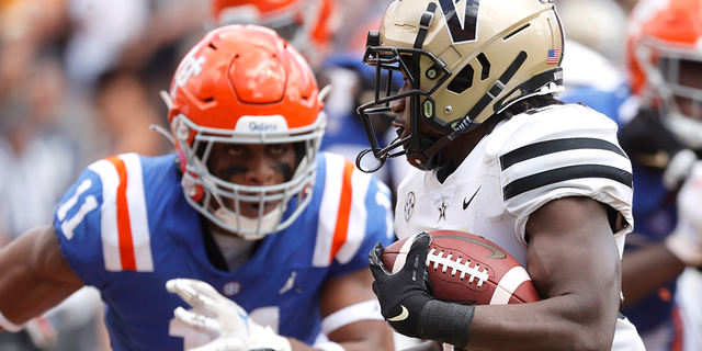 Oct 9, 2021; Gainesville, Florida, USA; Vanderbilt Commodores running back Rocko Griffin (24) runs with he ball as Florida Gators linebacker Mohamoud Diabate (11) defends during the second quarter at Ben Hill Griffin Stadium.