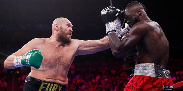 Tyson Fury, of England, hits Deontay Wilder in a heavyweight championship boxing match Saturday, Oct. 9, 2021, in Las Vegas.
