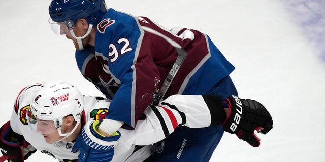 Colorado Avalanche left wing Gabriel Landeskog, top, holds Chicago Blackhawks left wing Dominik Kubalik and is called for a penalty during the second period of an NHL hockey game Wednesday, Oct. 13, 2021, in Denver.