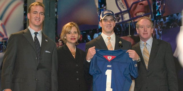 Eli Manning poses with a New York Giants jersey with his family during the 2004 NFL Draft at Madison Square Garden. Manning was selected No. 1 by the San Diego Chargers then traded to the New York Giants for Philip Rivers.