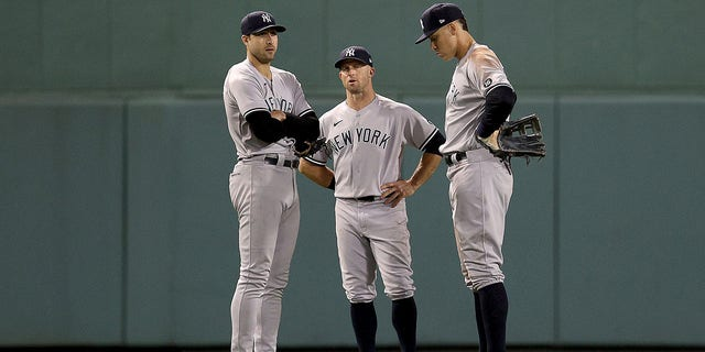 Joey Gallo #13,  Brett Gardner #11 and Aaron Judge #99 of the New York Yankees stand in the outfield during a pitching change against the Boston Red Sox during the seventh inning of the American League Wild Card game at Fenway Park on October 05, 2021 in Boston, Massachusetts.