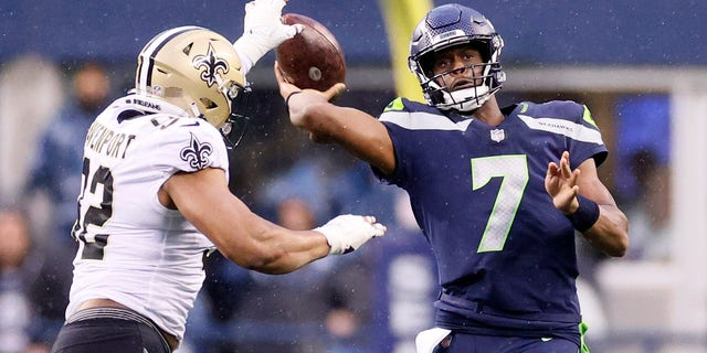 SEATTLE, WASHINGTON - OCTOBER 25: Geno Smith #7 of the Seattle Seahawks passes while pressured by Marcus Davenport #92 of the New Orleans Saints during the second quarter at Lumen Field on October 25, 2021 in Seattle, Washington. (Photo by Steph Chambers/Getty Images)