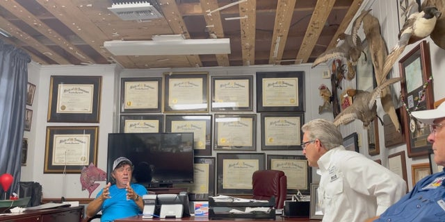 David Camardelle (D), Mayor of Grand Isle (left), speaks to local leaders in his office damaged by Hurricane Ida.