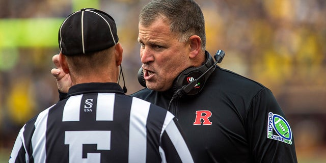 Rutgers head coach Greg Schiano speaks with a sideline official in the first quarter of an NCAA college football game against Michigan in Ann Arbor, Michigan, Saturday, Sept. 25, 2021.