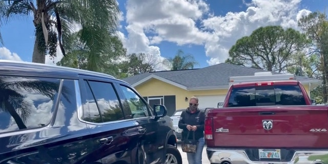 FBI agent carrying camoflauge bag out of Laundrie home (Fox News' Audrey Conklin)