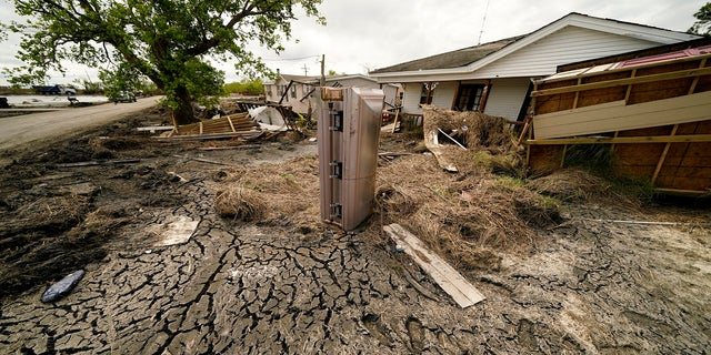 A casket that floated from its tombs during flooding from Hurricane Ida sits in a lawn of a destroyed home in Ironton, Louisiana, on Sept. 27.