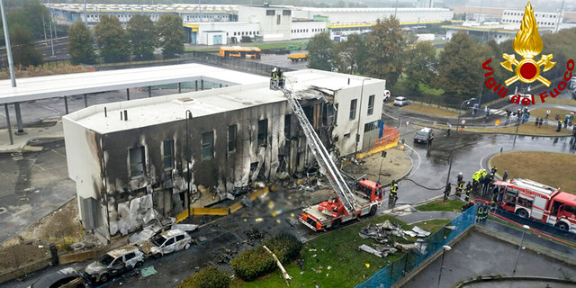 Firefighters work on the site of a plane crash, in San Donato Milanese suburb of Milan, Italy, Sunday, Oct. 3, 2021.