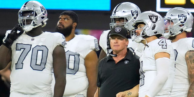 Las Vegas Raiders head coach Jon Gruden talks with quarterback Derek Carr (4) during the second half against the Los Angeles Chargers at SoFi Stadium.