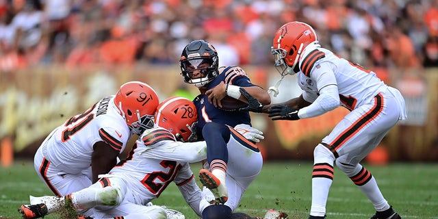 Chicago Bears quarterback Justin Fields slides for a short gain against Cleveland Browns defensive end Joe Jackson (91), linebacker Jeremiah Owusu-Koramoah (28) and cornerback Denzel Ward (21) during the second half of a game against the Cleveland Browns, Sunday, Sept. 26, 2021, in Cleveland.